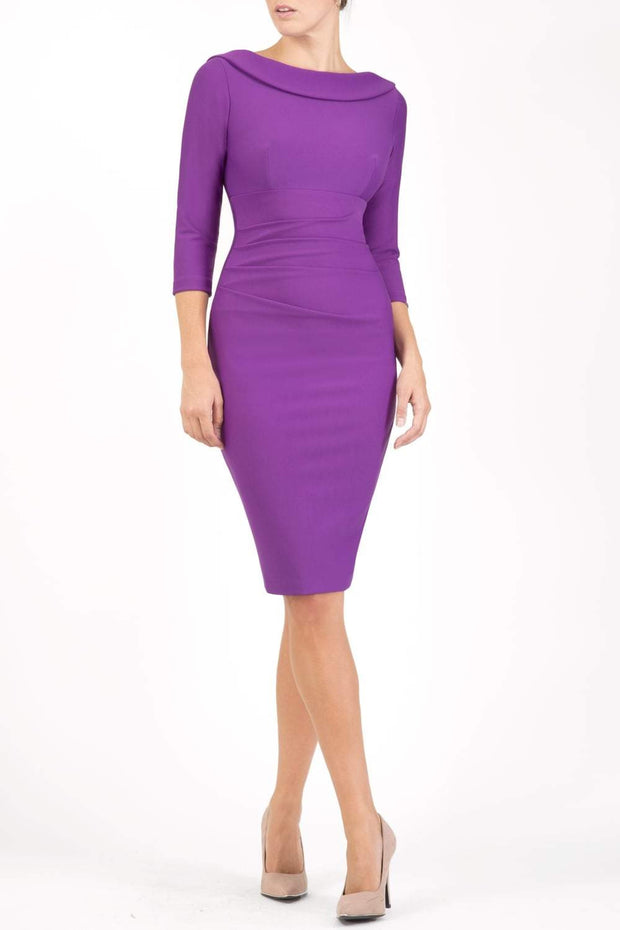 model wearing diva catwalk york pencil-skirt dress with sleeves and rounded folded collar and plearing across the tummy area in purple colour front
