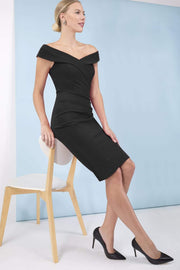brunette model wearing diva catwalk evening pencil skirt dress sleeveless with lowered neckline and pleating on side in black colour front