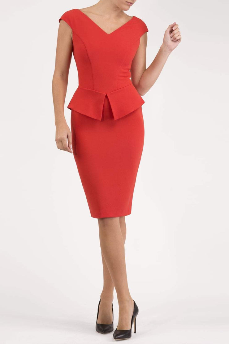 Model wearing the Diva Azalea Peplum dress with semi V neckline and peplum waistline in fiesta orange front image
