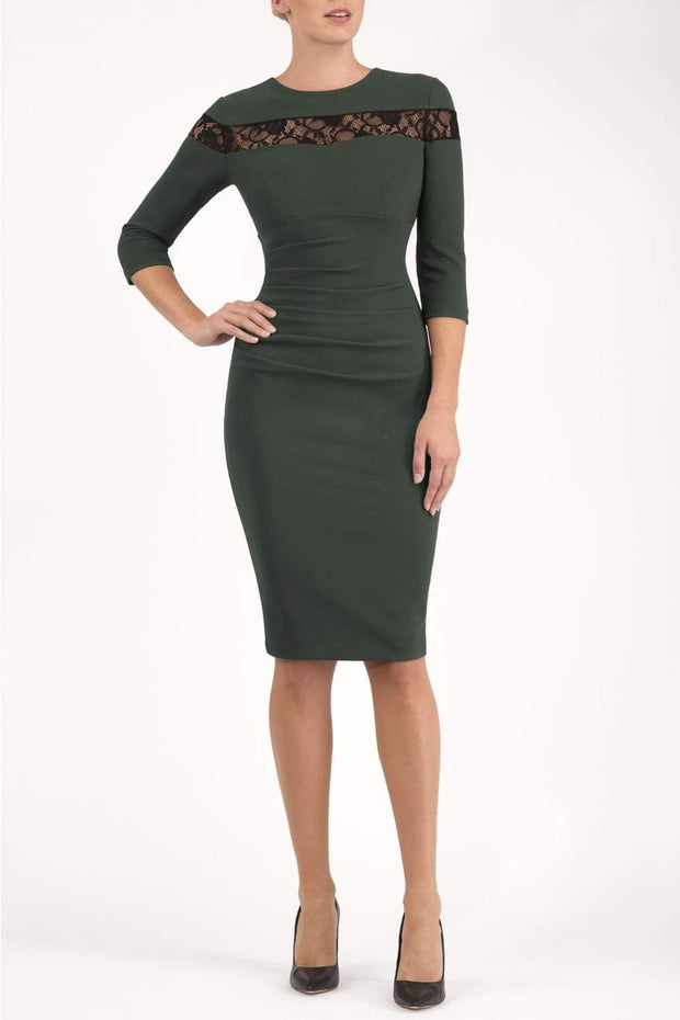 Model wearing the Diva Atlantis Pencil dress with three quarter length sleeves in deep green and black front image