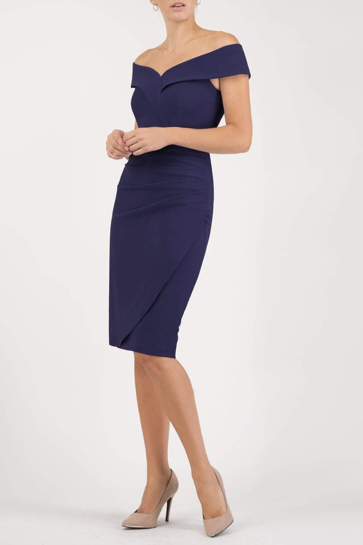 brunette model wearing diva catwalk evening pencil skirt dress sleeveless with lowered neckline and pleating on side in navy blue  colour front