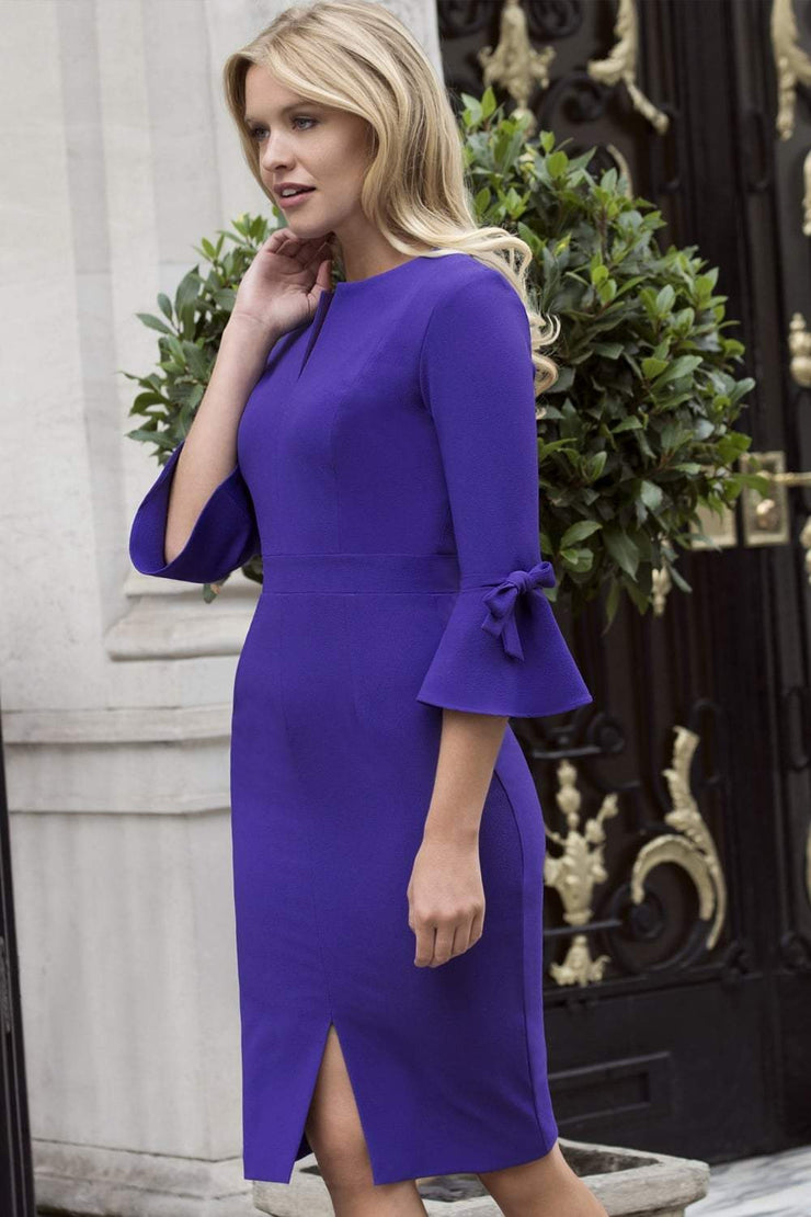 blonde model wearing diva catwalk zoe 3 4 sleeve formal dress with a split rounded neckline and split on skirt in spectrum indigo colour front