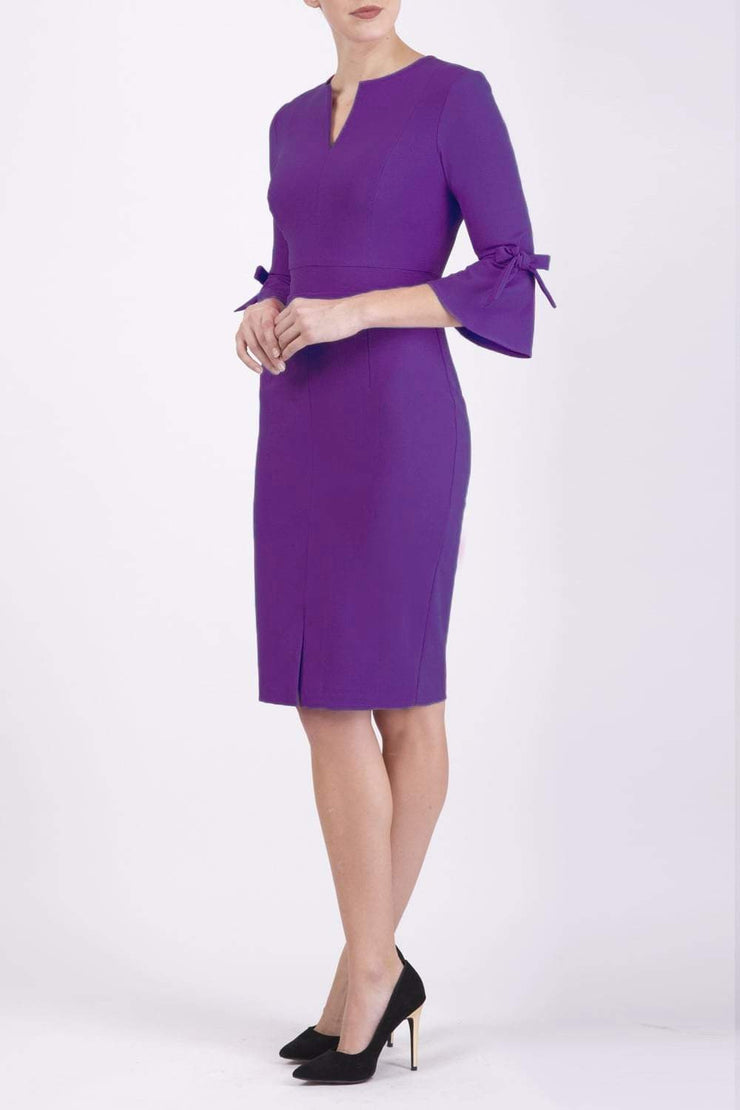 blonde model wearing diva catwalk zoe 3 4 sleeve formal dress with a split rounded neckline and split on skirt in passion purple colour front