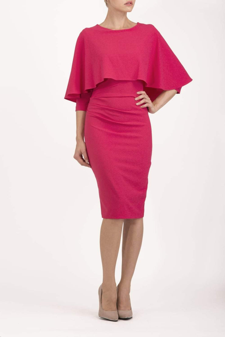 model wearing diva catwalk lizanne pencil-skirt dress with an attached wide cape detail and 3 4 sleeves in colour honeysuckle pink front