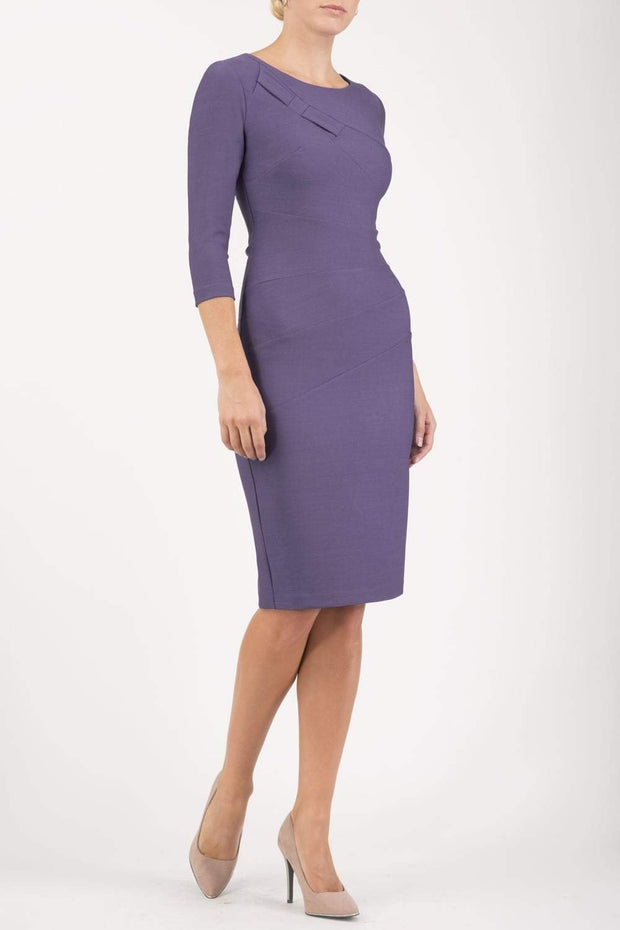 brunette model wearing diva catwalk couture althorp pencil fitted dress with sleeves and rounded neckline and bow detail at the top in lilac colour front