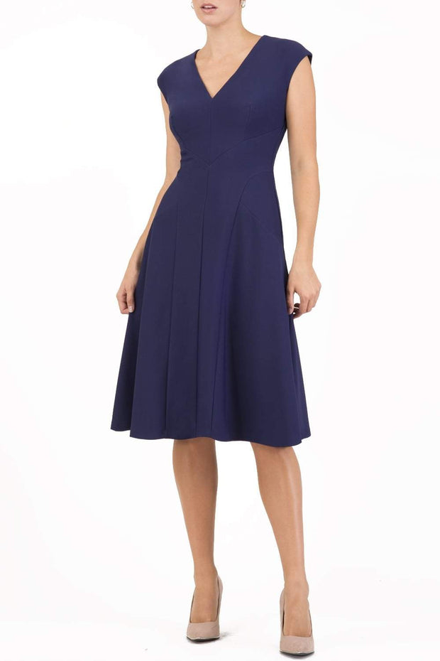 model wearing diva catwalk rochelle swing skirt a line dress without sleeves with a low v neck in navy front