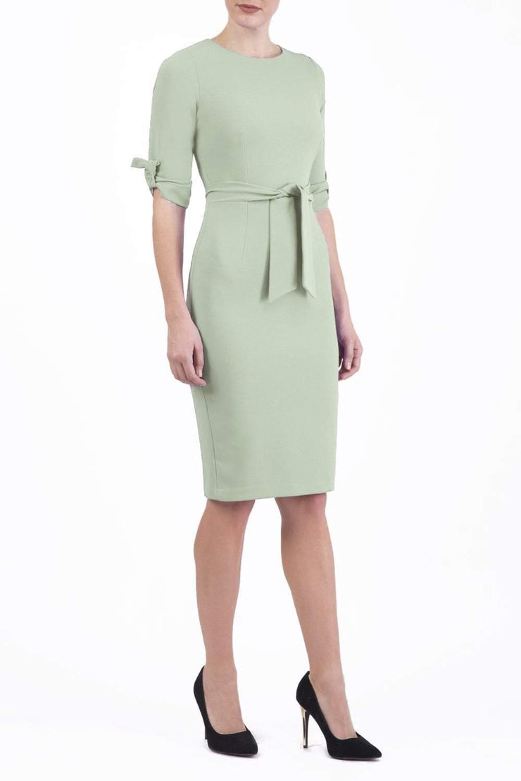 brunette model wearing diva catwalk tryst pencil deco green dress with sleeves and belt detail at the front with rounded neckline front
