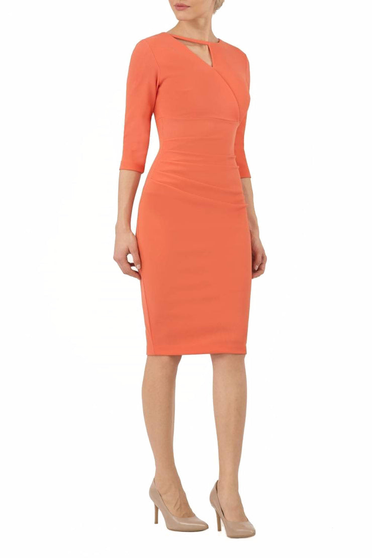 model wearing diva catwalk helston peach pencil dress with sleeves and cut out detail on the neckline front