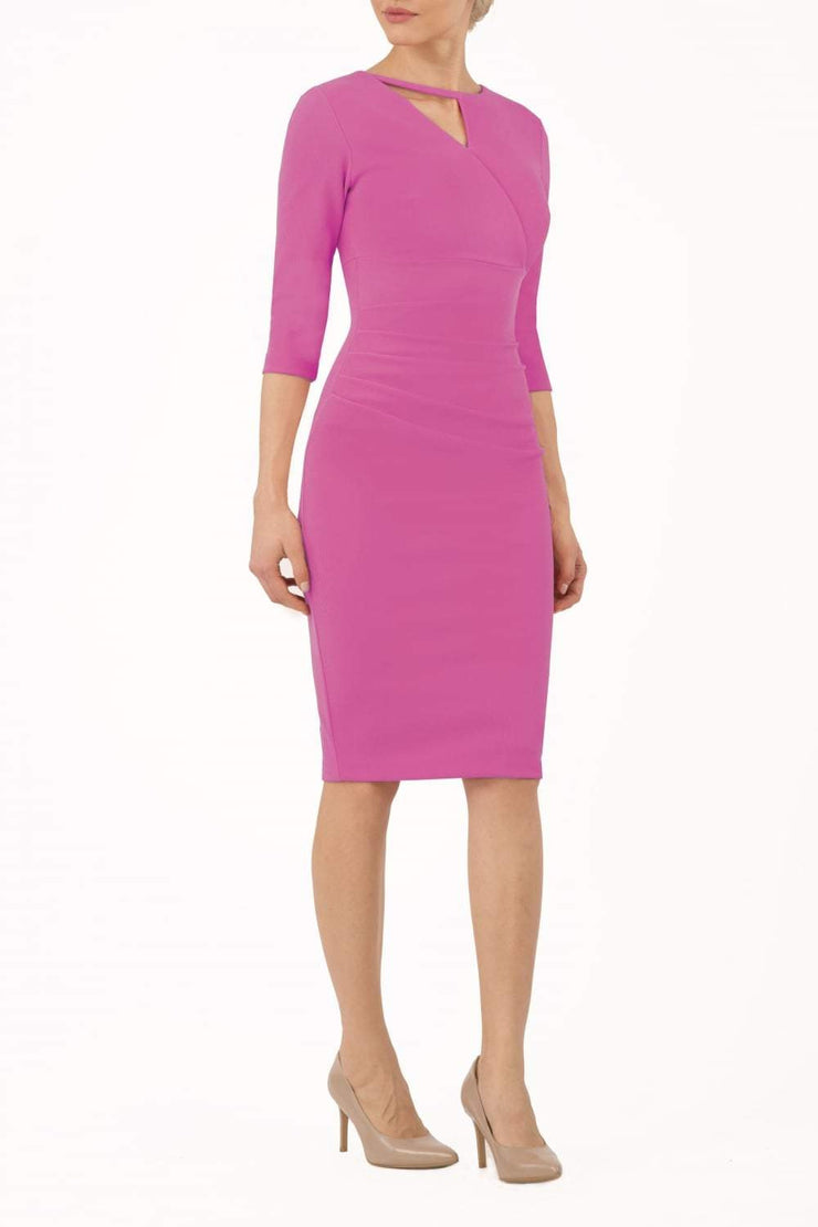 model wearing diva catwalk helston begonia pink pencil skirt  dress with sleeves and cut out detail on the neckline front