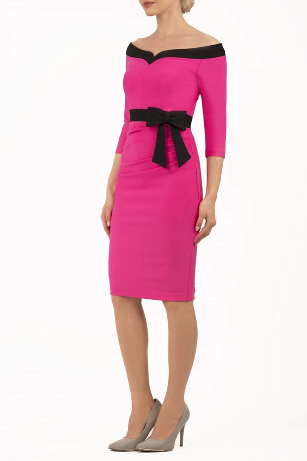 blonde model wearing diva catwalk luma pencil skirt dress with contrasting bow off shoulder with sleeves in hibiscus pink front