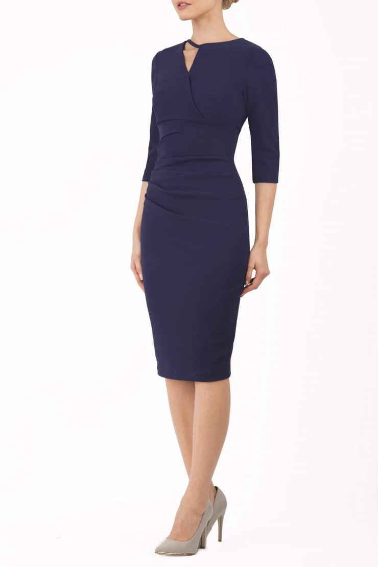 model wearing diva catwalk helston navy pencil skirt  dress with sleeves and cut out detail on the neckline front