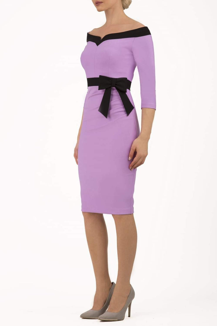 blonde model wearing diva catwalk luma pencil skirt dress with contrasting bow off shoulder with sleeves in violet bloom front