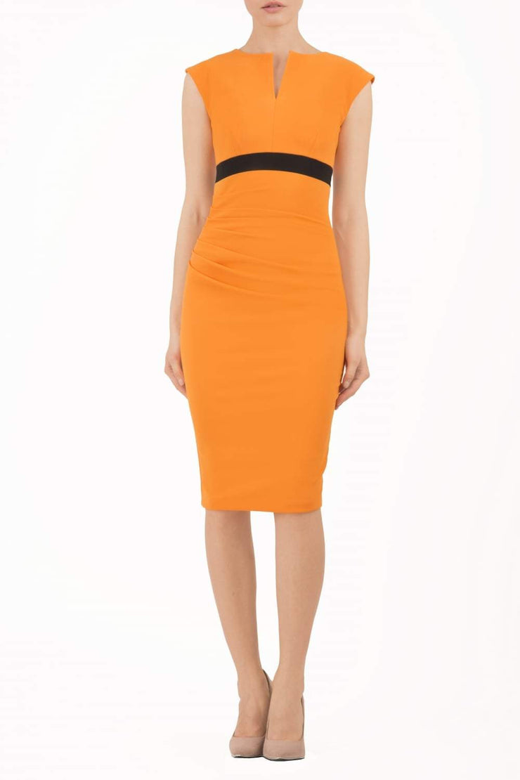 brunette model wearing diva catwalk nadia sleeveless pencil dress in sun orange colour with a contrasting black band and exposed zip at the back with a rounded neckline with a slit  in the middle front