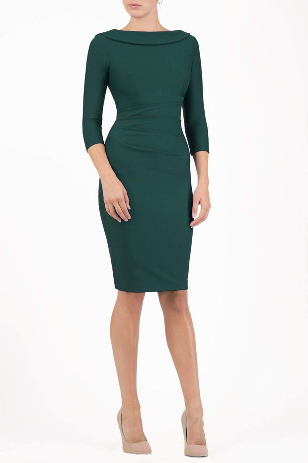 model wearing diva catwalk york pencil-skirt dress with sleeves and rounded folded collar and plearing across the tummy area in forest green colour front
