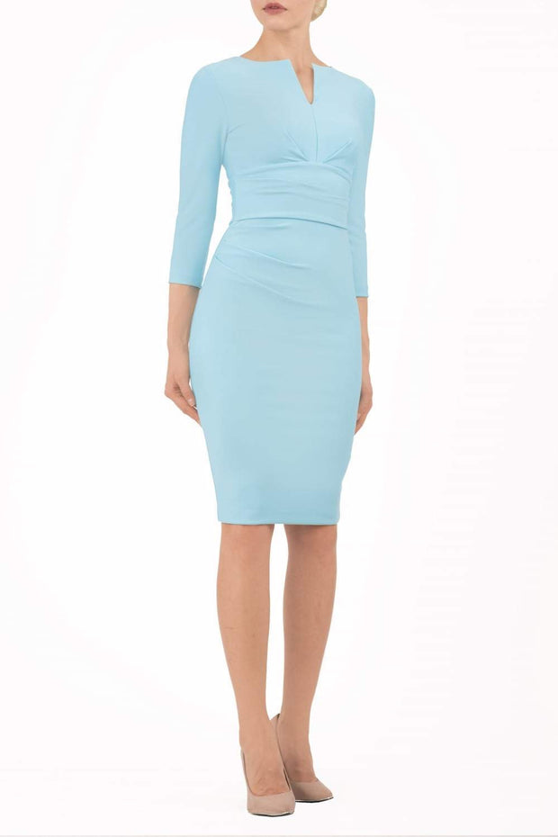 model wearing diva catwalk donna pencil dress in pale blue colour with wide band and sleeves and rounded neckline with low split in front