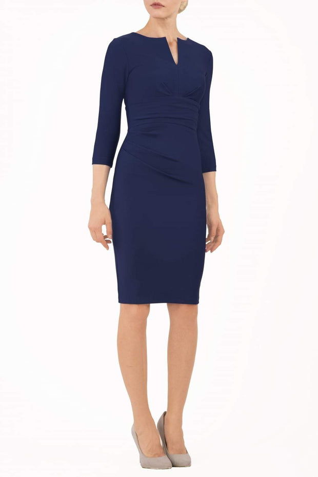 model wearing diva catwalk donna pencil dress in navy blue colour with wide band and sleeves and rounded neckline with low split in front