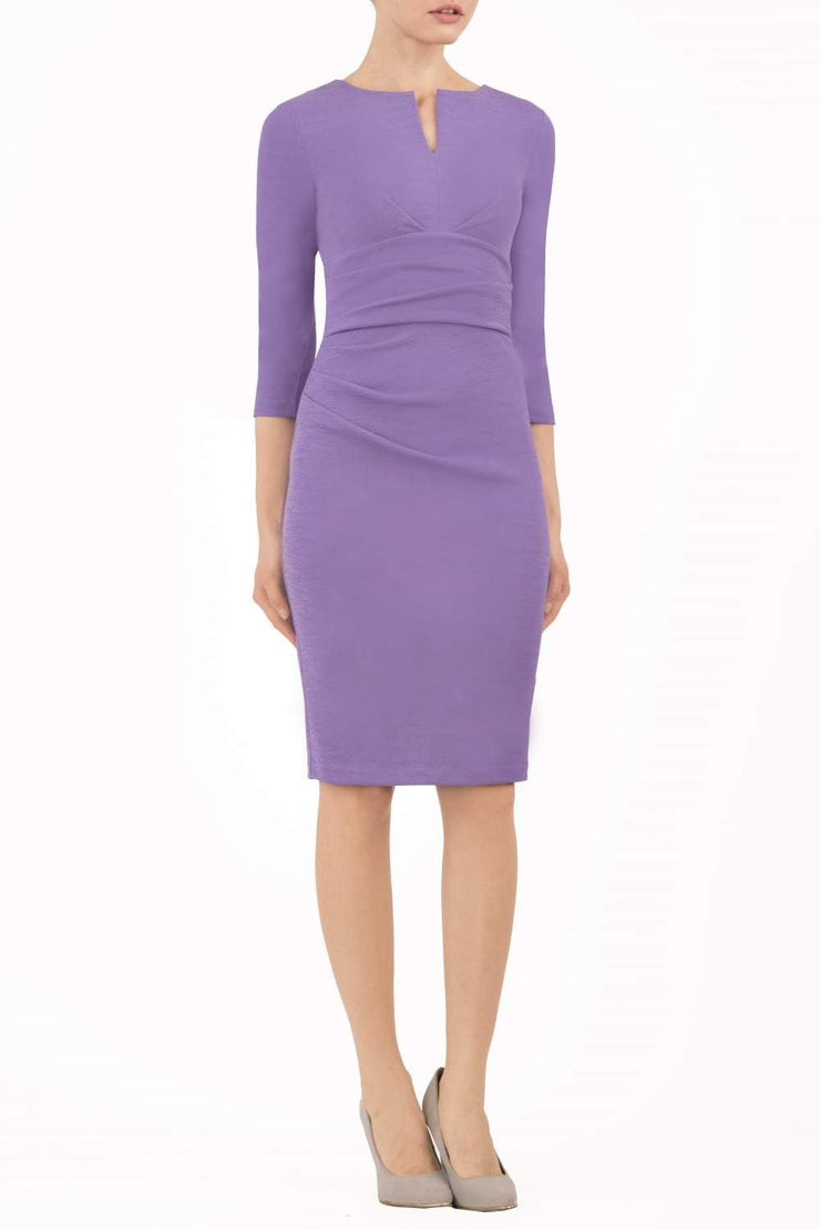 model wearing diva catwalk donna pencil dress in colour purple with wide band and sleeves and rounded neckline with low split in front