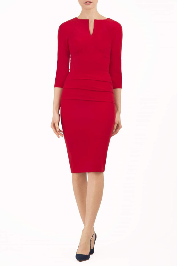 Model wearing the Diva Daphne Venice Stretch Pencil dress with pleat detail across the front in tango red front image