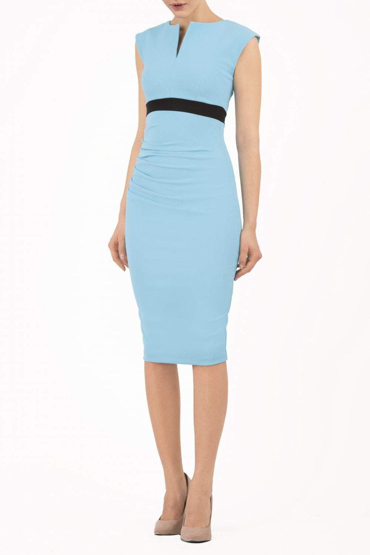 brunette model wearing diva catwalk nadia sleeveless pencil dress in sky blue colour with a contrasting black band and exposed zip at the back with a rounded neckline with a slit  in the middle front