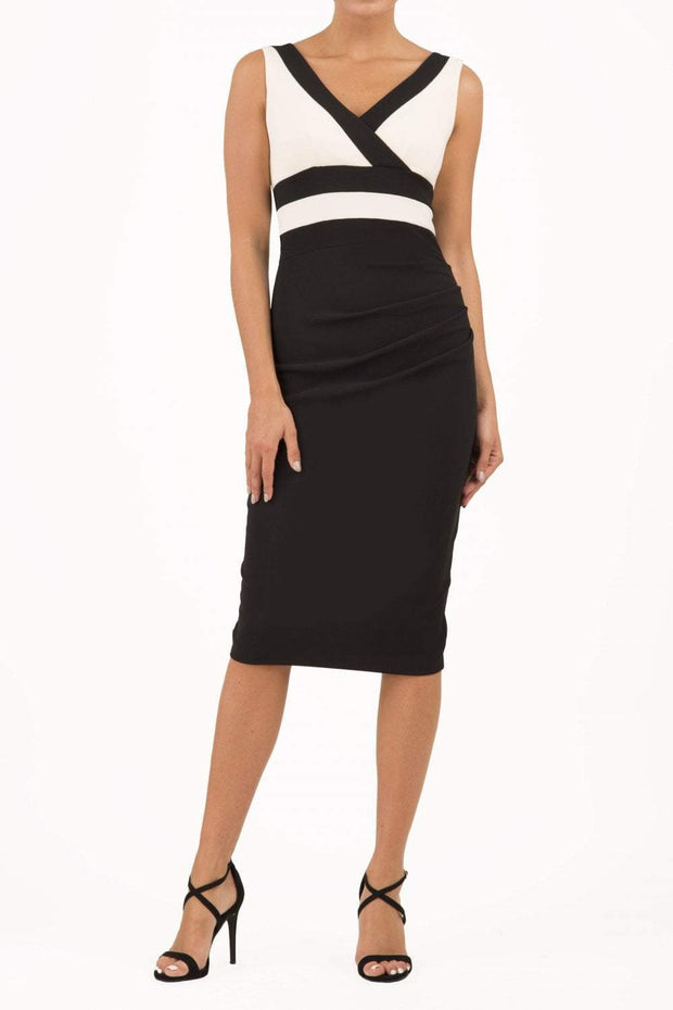 Model wearing the Diva Banbury Colour block dress with bust panels in contrast and pleating across the front in black and vanilla cream front image