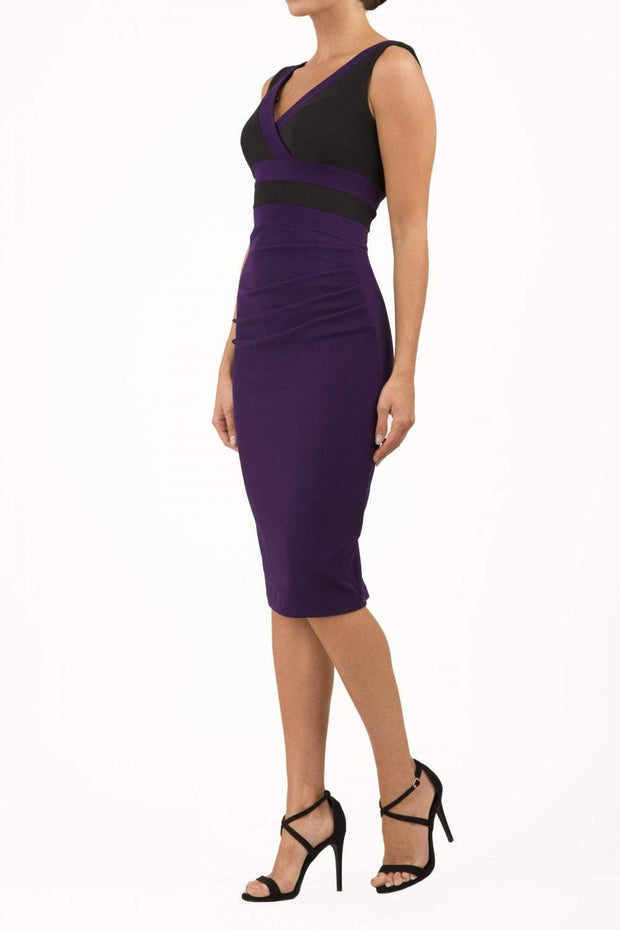 Model wearing the Diva Banbury Colour block dress with bust panels in contrast and pleating across the front in black and violet front image