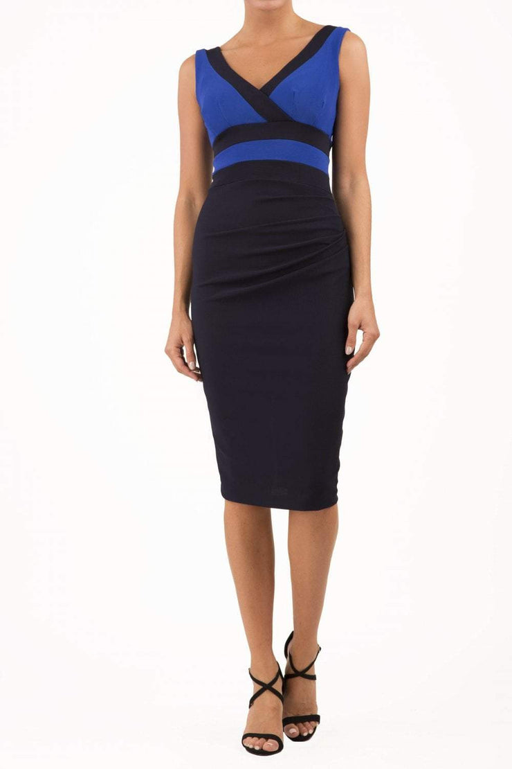 Model wearing the Diva Banbury Colour block dress with bust panels in contrast and pleating across the front in black and cobalt front image