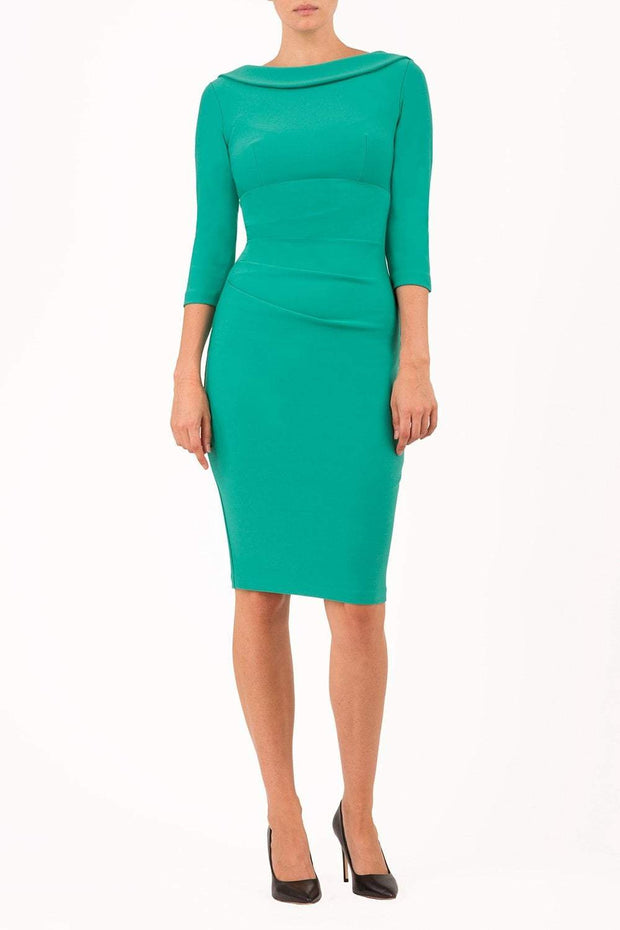 model wearing diva catwalk york pencil-skirt dress with sleeves and rounded folded collar and plearing across the tummy area in emerald green colour front