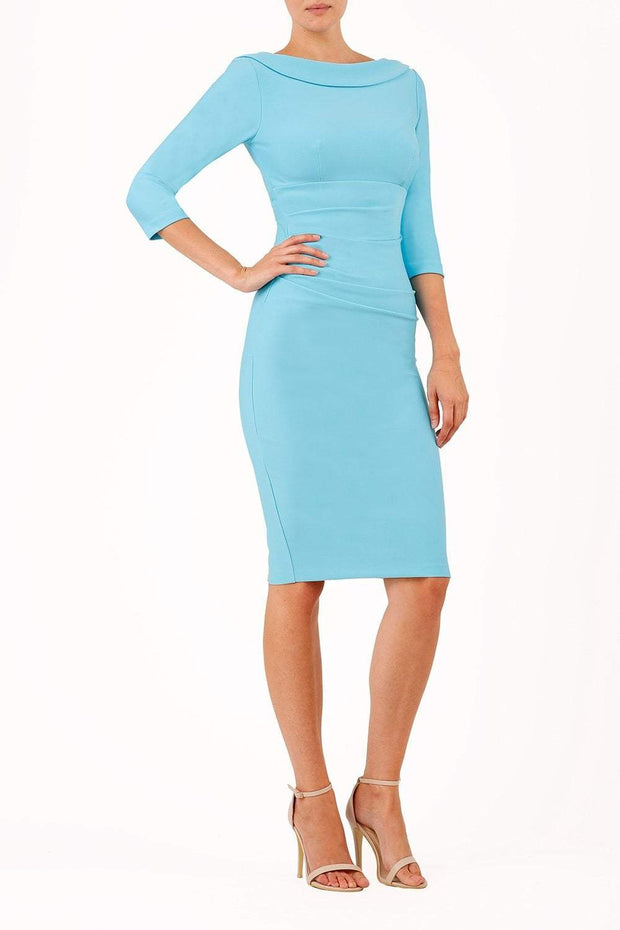 model wearing diva catwalk york pencil-skirt dress with sleeves and rounded folded collar and plearing across the tummy area in sky blue colour front