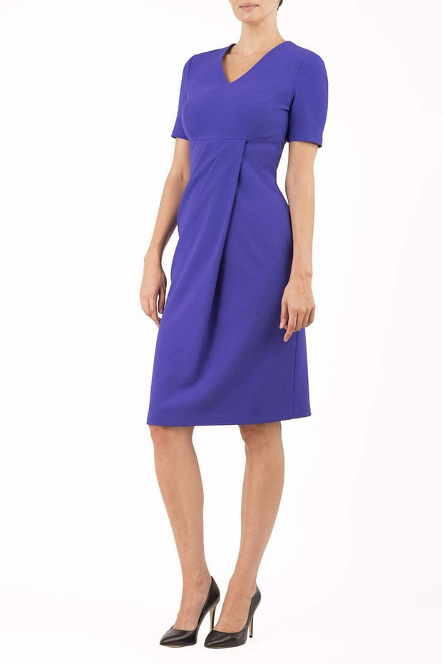 brunette model wearing diva catwalk tregony a-line dress with lowered v-neckline in spectrum indigo and short sleeves front