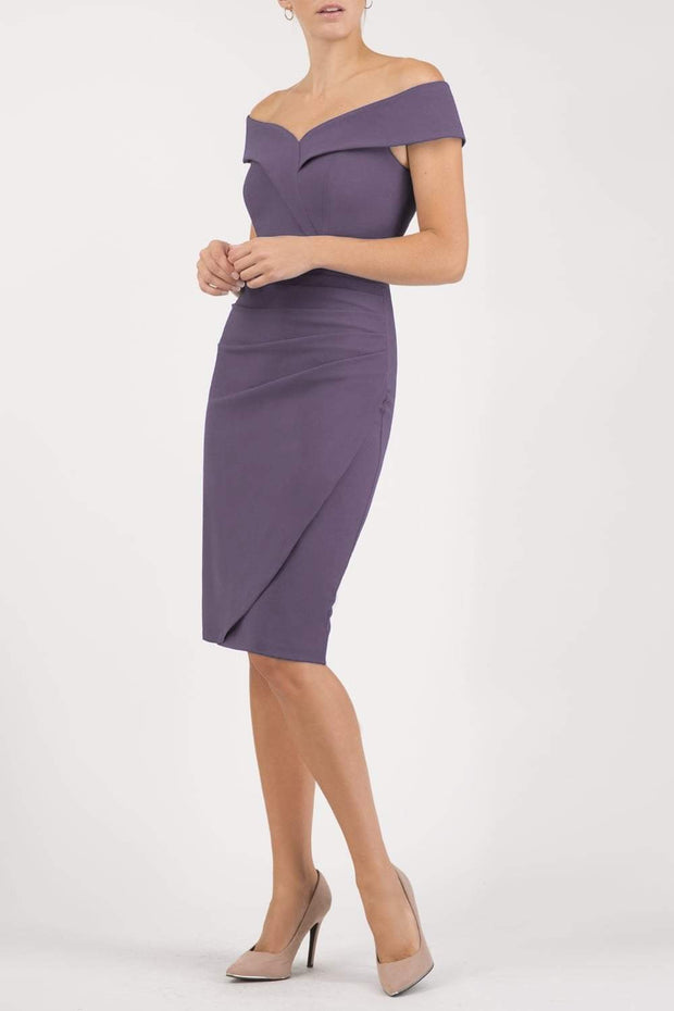 brunette model wearing diva catwalk evening pencil skirt dress sleeveless with lowered neckline and pleating on side in dark mauve colour front