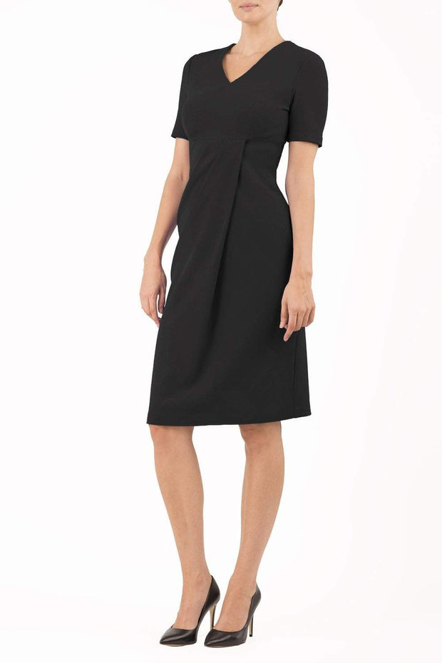 brunette model wearing diva catwalk tregony a-line dress with lowered v-neckline in black and short sleeves front