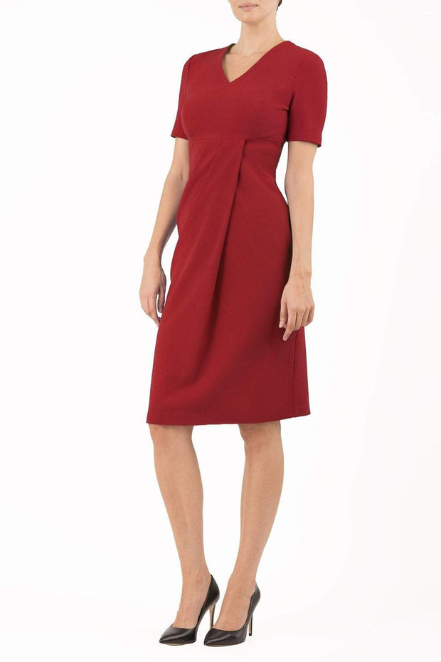 brunette model wearing diva catwalk tregony a-line dress with lowered v-neckline in passion red and short sleeves front
