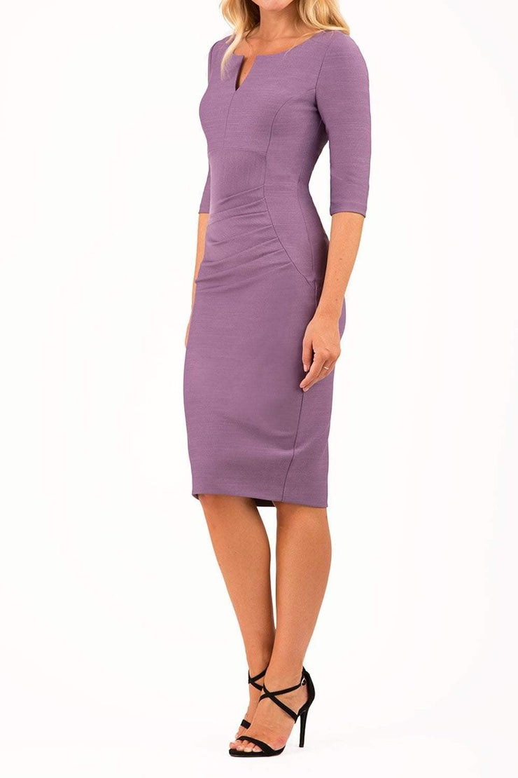 model wearing seed couture royale pencil skirt dress with pleating across the tummy area with rounded neckline with a split in the middle and 3 4 sleeve in dusky lilac colour front