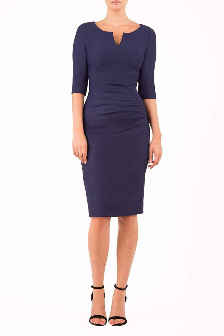 model wearing seed couture royale pencil skirt dress with pleating across the tummy area with rounded neckline with a split in the middle and 3 4 sleeve in navy blue colour front