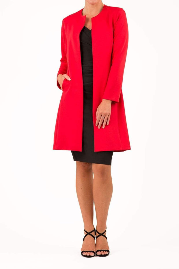 model wearing diva catwalk red coat with long sleeves and a belt front