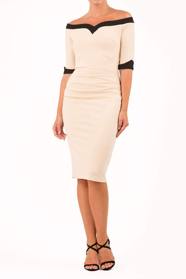 blonde model is wearing diva catwalk fellini sweetheart neckline fitted pencil dress with sleeves with cuff in colour beige with black contrasting detail front