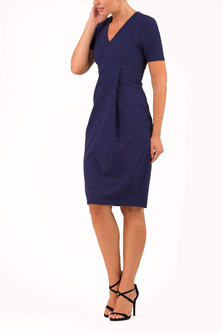 brunette model wearing diva catwalk tregony a-line dress with lowered v-neckline in oxford blue and short sleeves front