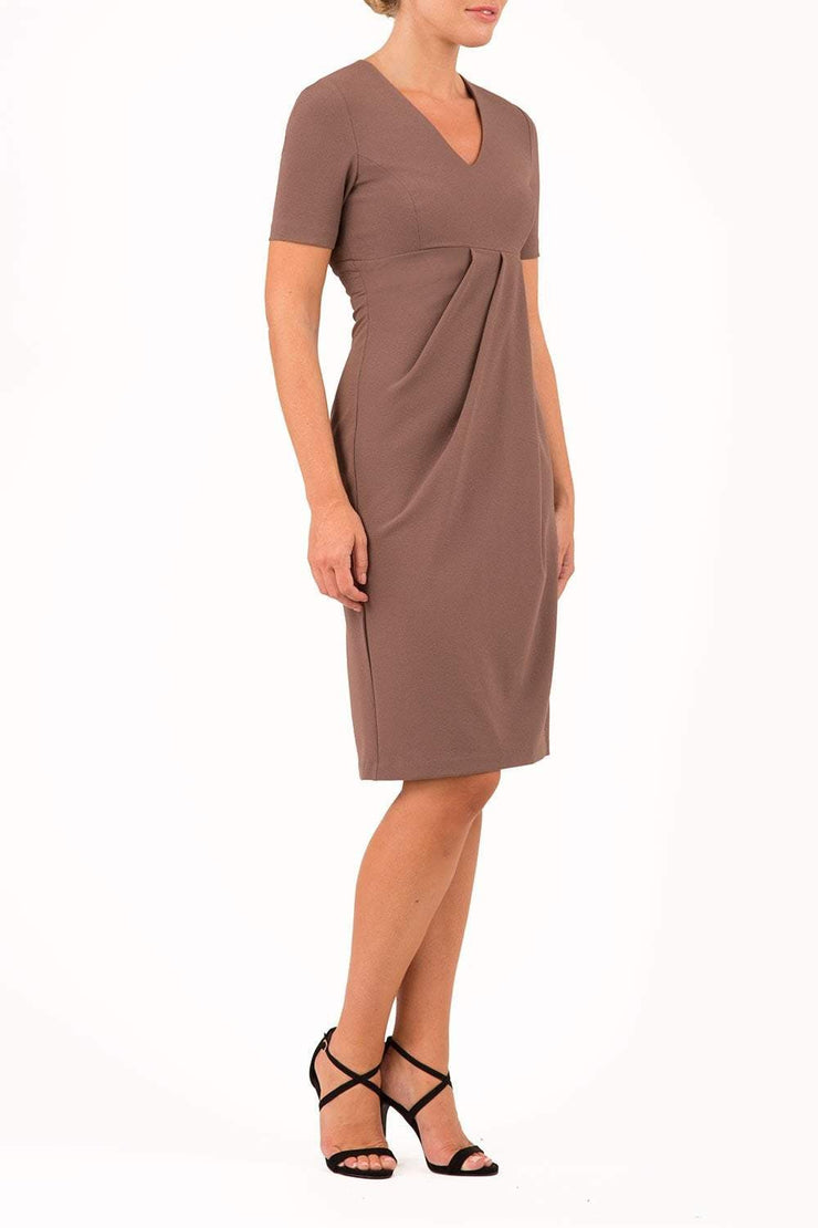 brunette model wearing diva catwalk tregony a-line dress with lowered v-neckline in brown and short sleeves front