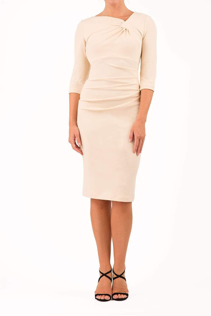 brinette model wearing diva catwalk kubrick pencil-skirt dress with sleeves and asymmetric neckline in beige front