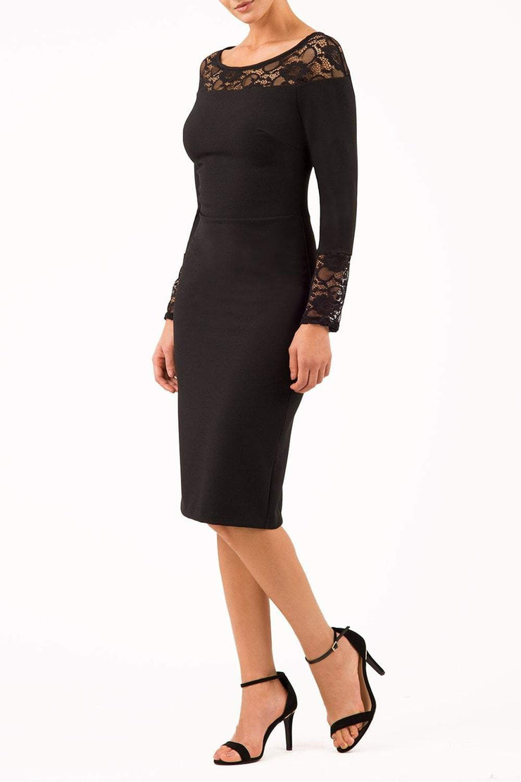 brunette model wearing diva catwalk black lace pencil dress with long sleeves and rounded lace neckline with the lace covering shoulders front