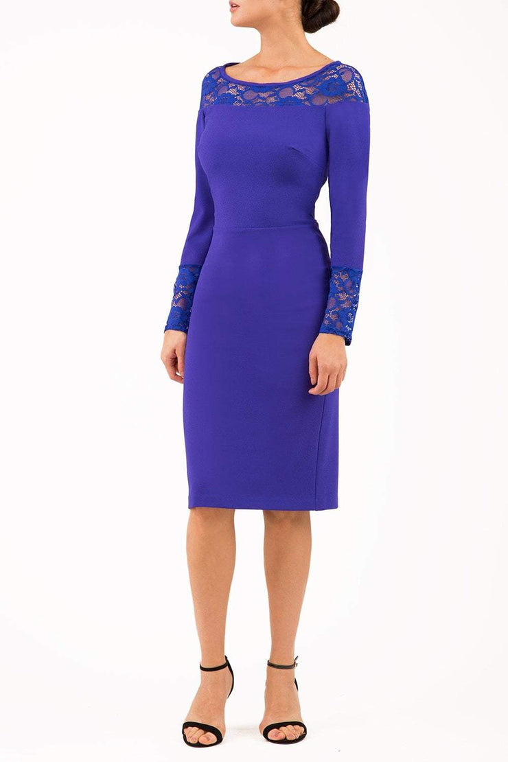 brunette model wearing diva catwalk blue lace pencil dress with long sleeves and rounded lace neckline with the lace covering shoulders front