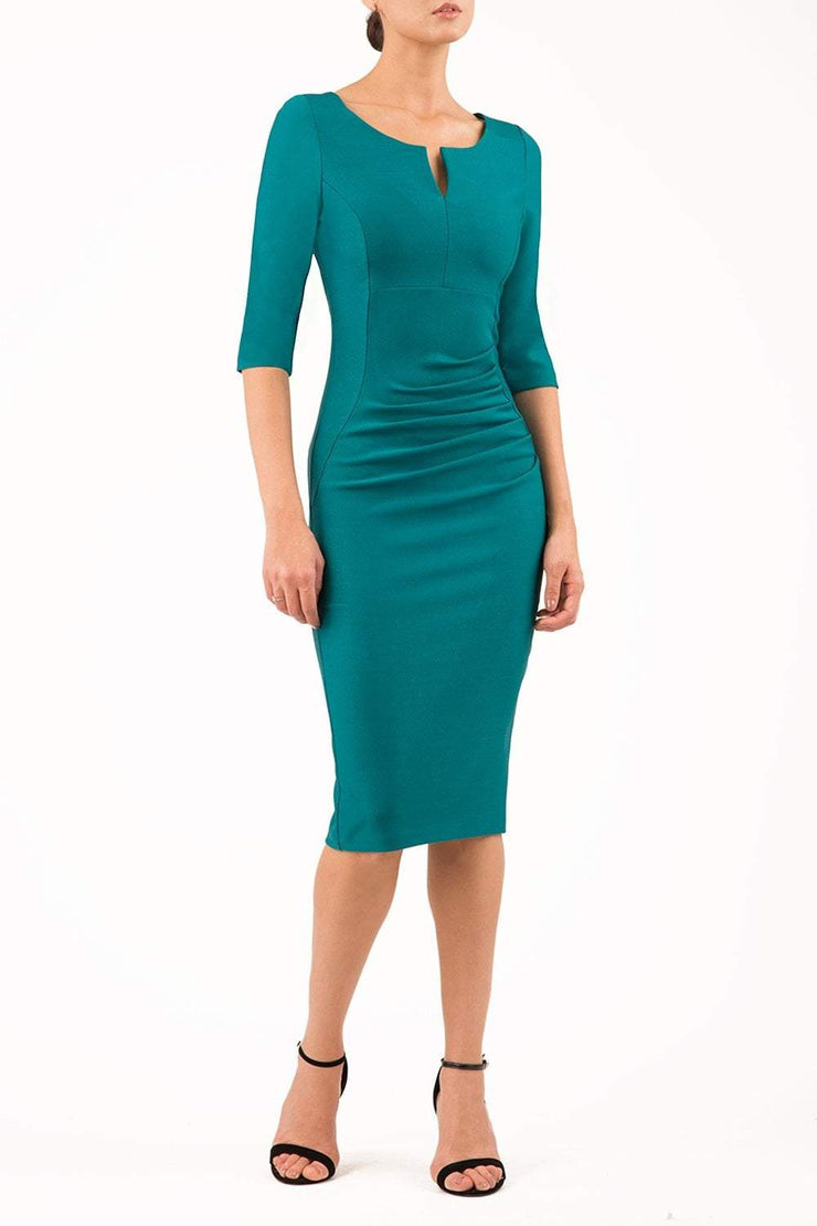model wearing seed couture royale pencil skirt dress with pleating across the tummy area with rounded neckline with a split in the middle and 3 4 sleeve in green colour front