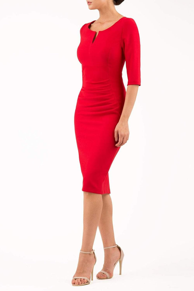 model wearing seed couture royale pencil skirt dress with pleating across the tummy area with rounded neckline with a split in the middle and 3 4 sleeve in red colour front