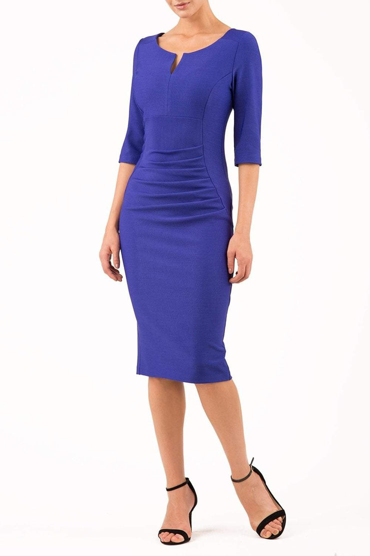model wearing seed couture royale pencil skirt dress with pleating across the tummy area with rounded neckline with a split in the middle and 3 4 sleeve in royal blue colour front