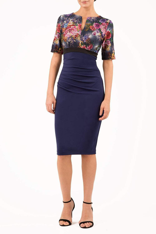 model wearing diva catwalk nadia fitted pencil dress made in the uk with short sleeves and pleated pencil skirt in navy and black front