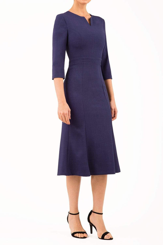 blonde model is wearing diva catwalk senne midaxi sleeved dress with fishtail and rounded neckline with a slit in the middle in navy front