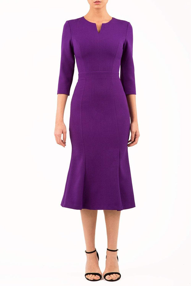 blonde model is wearing diva catwalk senne midaxi sleeved dress with fishtail and rounded neckline with a slit in the middle in purple front