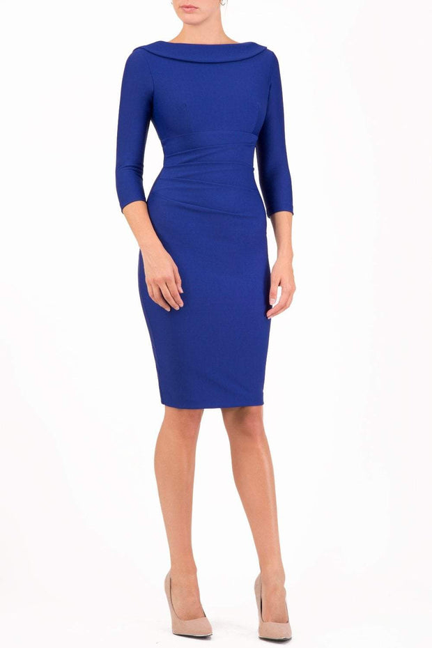 model wearing diva catwalk york pencil-skirt dress with sleeves and rounded folded collar and plearing across the tummy area in cobalt blue colour front