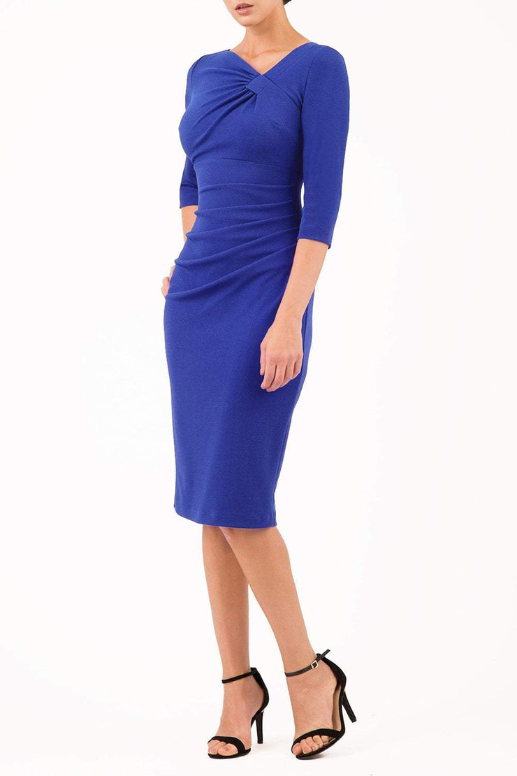 brinette model wearing diva catwalk kubrick pencil-skirt dress with sleeves and asymmetric neckline in cobalt blue front