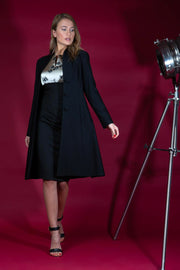 brunette model wearing diva catwalk couture fine raquella coat with buttons across the front and long sleeves with high neck and pockets in black colour front  Edit alt text